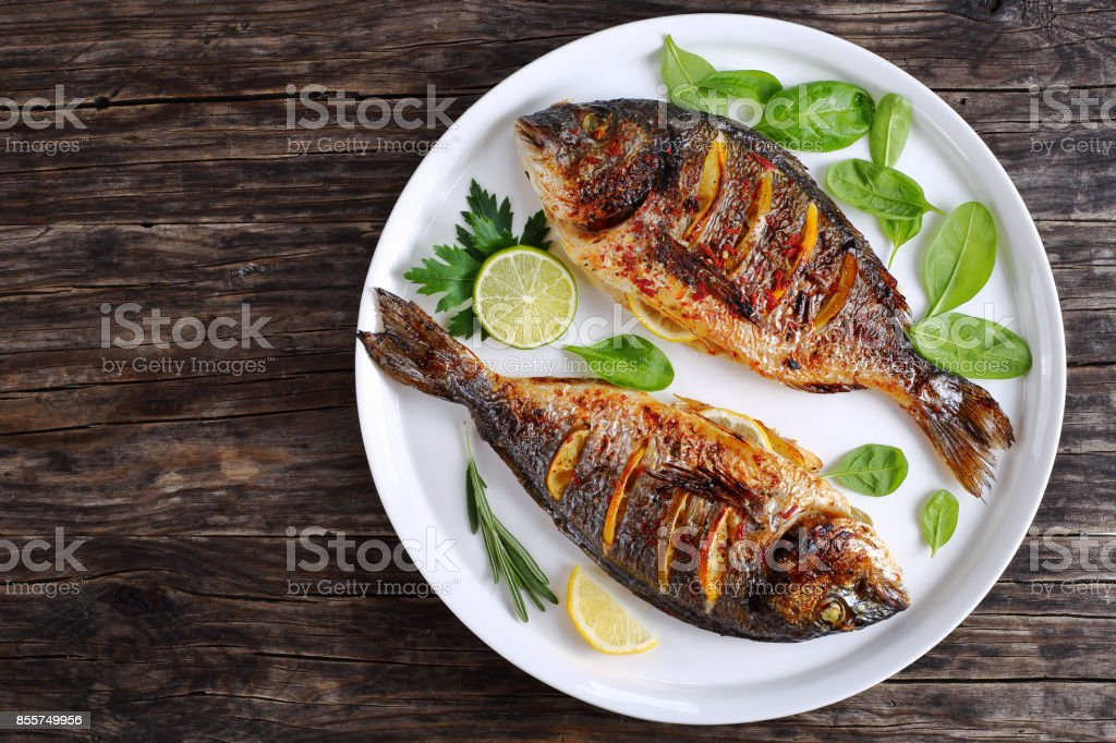 roasted sea bream fish with lemon slices stock photo
