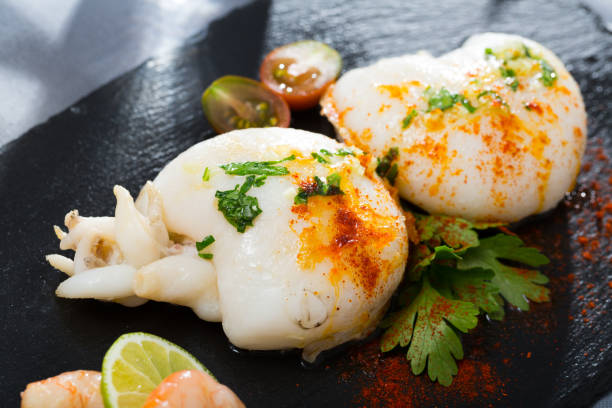 Roasted sepia served with shrimps Delicious seafood dish - roasted cuttle served with lime, shrimps, cherry tomato and parsley cuttlefish stock pictures, royalty-free photos & images