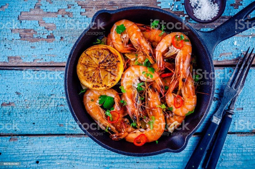 Roasted shrimps with parsley, chili pepper, garlic and lemon stock photo