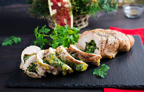 Gebratene sinierte Weihnachtsrolle mit Spinat und Käse auf dunklem rustikalen Hintergrund.  Festival Essen. – Foto