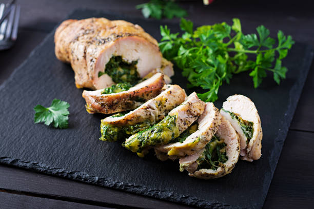Roasted sliced Christmas roll of turkey with spinach and cheese on dark rustic background.  Festival food. stock photo