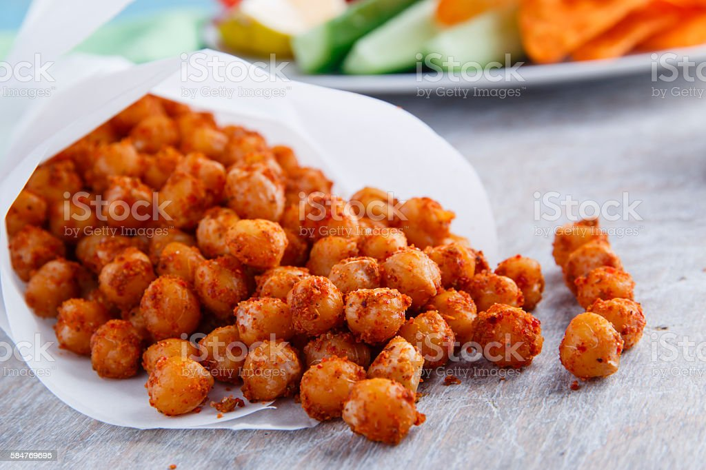 Roasted spicy chickpeas on a wooden surface stock photo
