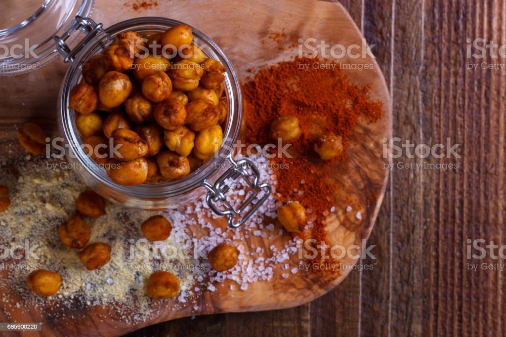 Roasted spicy chickpeas on rustic background stock photo