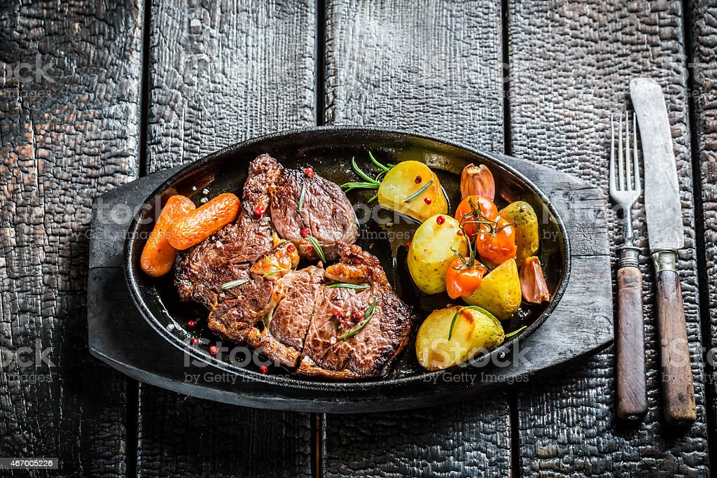 Roasted steak and vegetables with herbs on grill stock photo