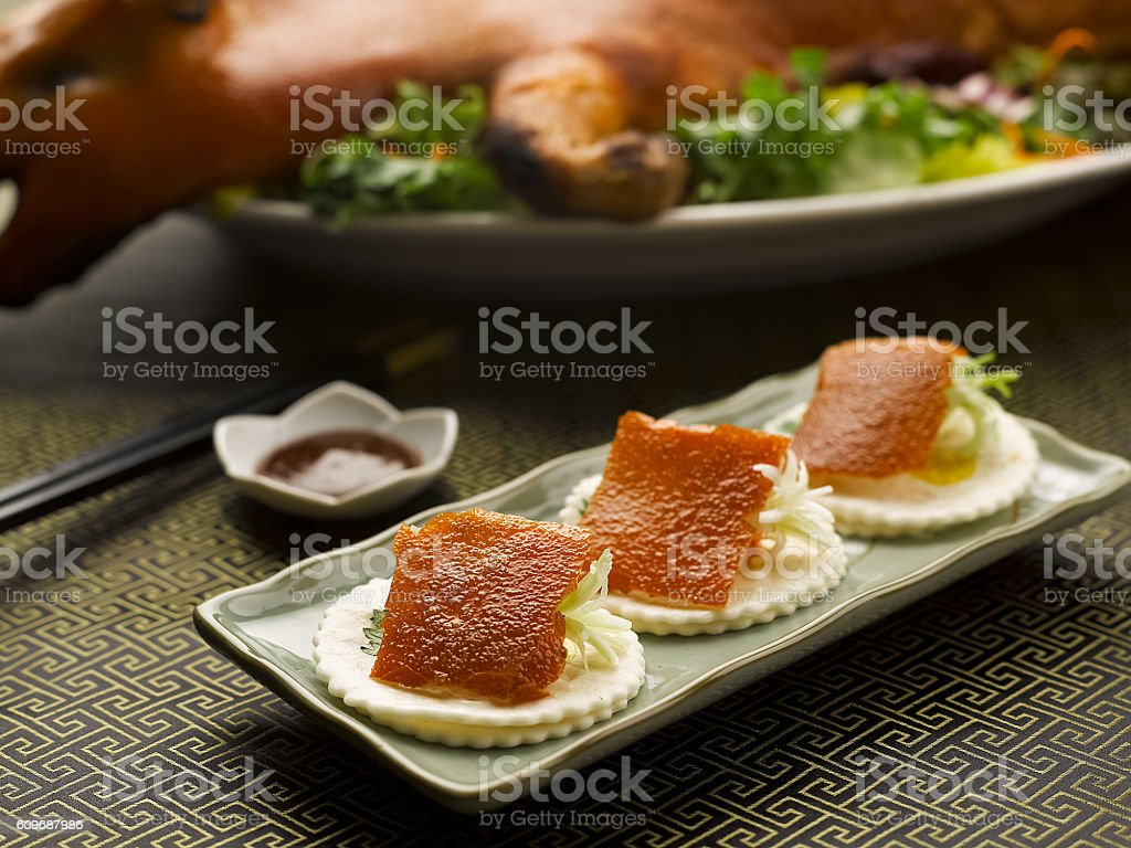 Roasted Suckling Pig skin with onion and crackers on dish stock photo