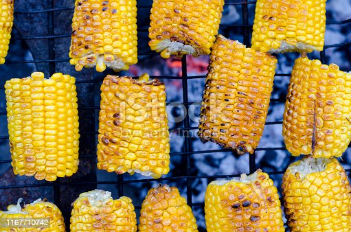Fresh yellow corn is cooked lying on the grill and cooked on the grill. Close-up