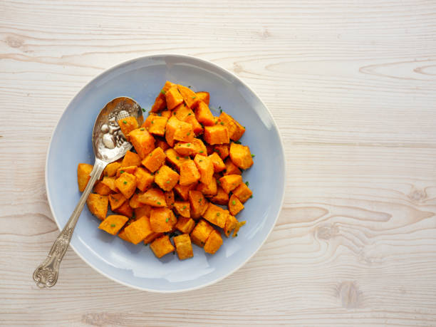 Roasted sweet potatoes salad Home made freshness roasted sweet potatoes cubes with fine chopped chives sweet potato stock pictures, royalty-free photos & images