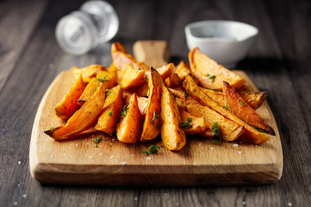 roasted Sweet potatoes wedges Home made freshness roasted sweet potatoes wedges with garlic herbs sweet potato stock pictures, royalty-free photos & images