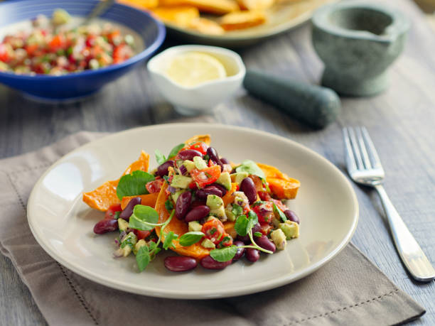 Roasted sweet potatoes wedges with guacamole and kidney beans stock photo