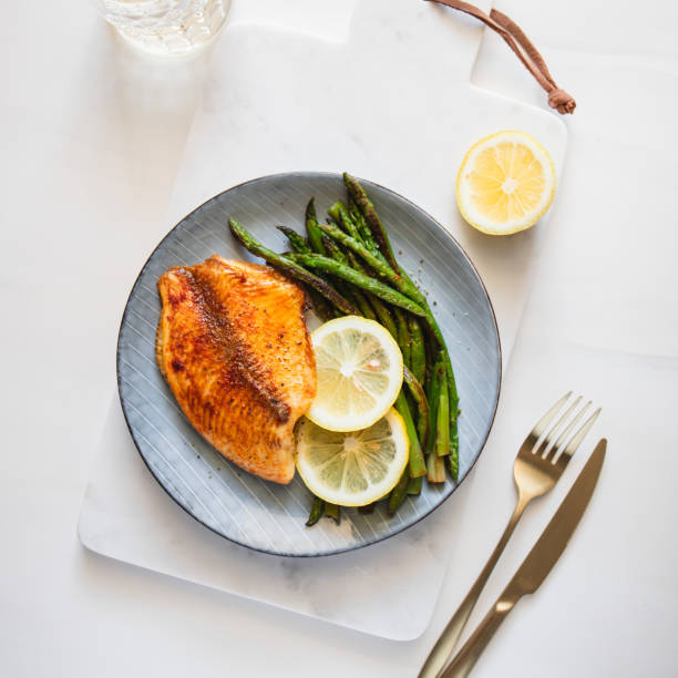 Roasted tilapia fish with asparagus on a white marble tray. Healthy mediterranean diet lunch or dinner. Top view, flat lay. stock photo