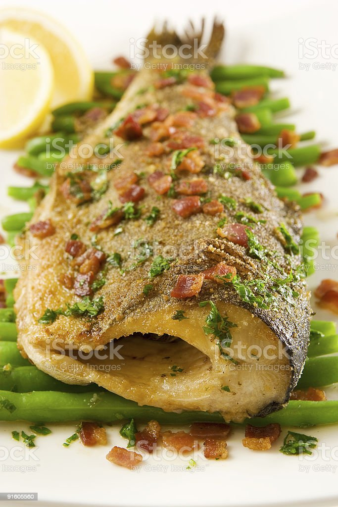 Roasted trout with bacon and greens royalty-free stock photo