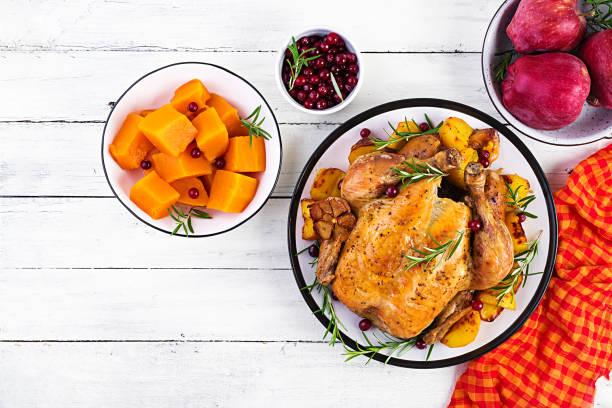 Gebratener Truthahn garniert mit Preiselbeeren auf einem rustikalen Tisch, der mit Herbstblatt dekoriert ist. Thanksgiving-Tag. Gebackenes Huhn. Ansicht von oben – Foto
