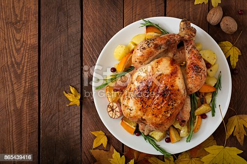 istock Roasted turkey garnished with cranberries on a rustic style table decorated with pumpkins, orange, apples and autumn leaf. Thanksgiving Day. Flat lay. Top view 865439416