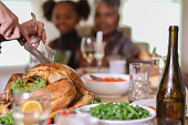 Man carves the roasted turkey on platter during Thanksgiving or Christmas dinner.  Vegetables and trimmings around turkey.