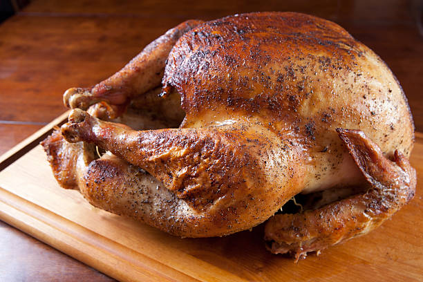 Roasted Turkey Resting on Wooden Board stock photo