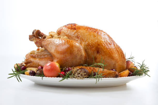 pavo asado con manzanas agarradas sobre blanco - thanksgiving turkey fotografías e imágenes de stock