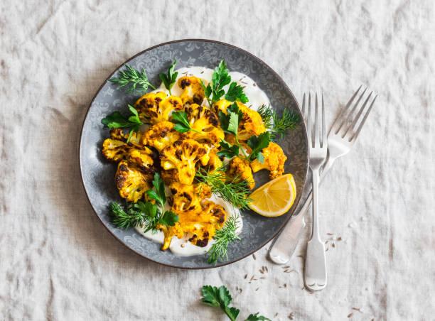geröstete kurkum-kohlenkohl mit griechischem joghurt-dressing. leckeres gesundes essen auf grauem hintergrund, top-ansicht - gebackener blumenkohl stock-fotos und bilder