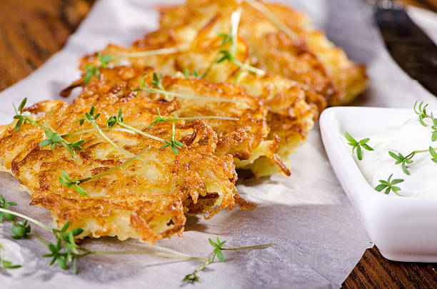 Roasted vegetable fritters Potato pancakes with green sprouts on a sheet of parchment fritter stock pictures, royalty-free photos & images