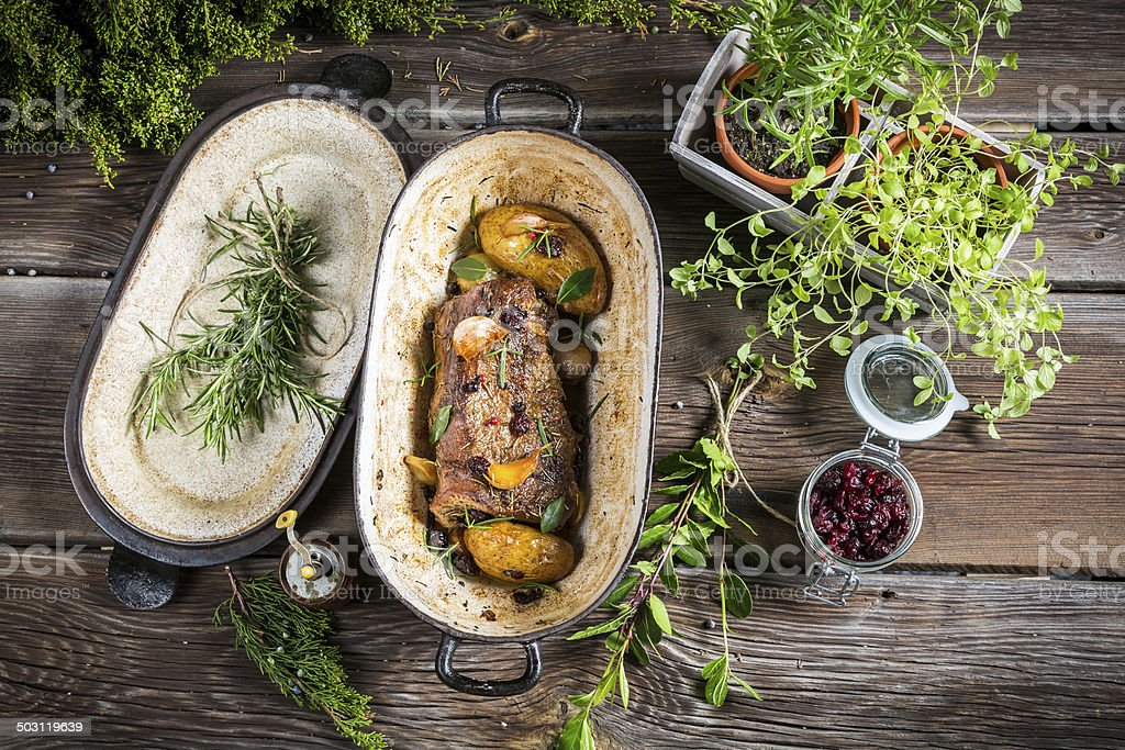 Roasted venison with herbs and vegetables stock photo
