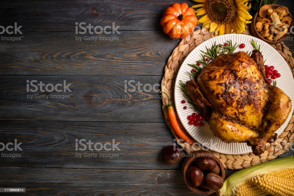 Roasted whole chicken or turkey with autumn vegetables for thanksgiving dinner on wooden background. Thanksgiving Day concept. Top view - Zbiór zdjęć royalty-free (Bankiet)