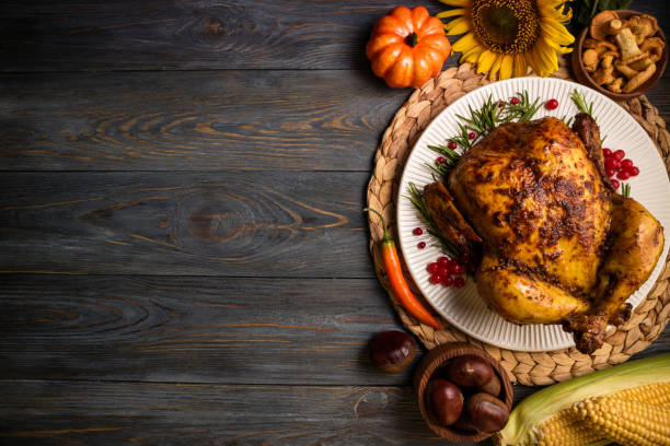 roasted whole chicken or turkey with autumn vegetables for thanksgiving dinner on wooden background. thanksgiving day concept. top view - thanksgiving стоковые фото и изображения