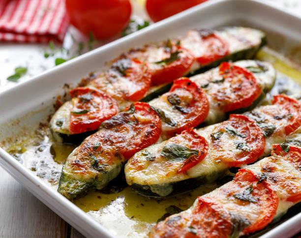 gebratene zucchini mit tomaten, mozzarella-käse, frischem basilikum und olivenöl (caprese-salat) in einer keramikbackform, nahaufnahme. - gefüllte zucchini vegetarisch stock-fotos und bilder