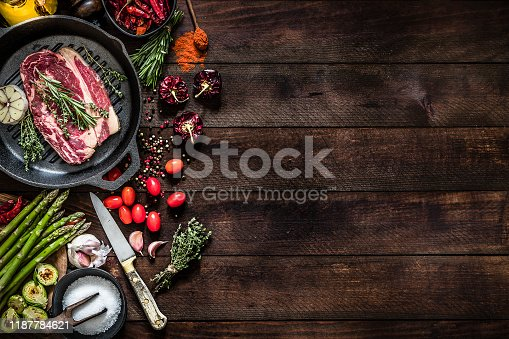 Top view of an iron grill with a beef steak, aromatic herbs and garlic surrounded by vegetables like tomatoes, asparagus and roasted Brussel sprouts, salt and pepper, aromatic herbs like thyme and rosemary and a kitchen knife on a dark brown rustic wooden table. Objects are at the left of the image leaving a useful copy space for a text or a logo at the opposite side on the backdrop. Low key DSLR photo taken with Canon EOS 6D Mark II and Canon EF 24-105 mm f/4L