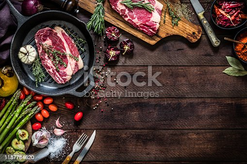 Top view of an iron grill with a beef steak, aromatic herbs and garlic surrounded by vegetables like tomatoes, asparagus and roasted Brussel sprouts, salt and pepper, aromatic herbs like thyme and rosemary, a kitchen knife and a wooden cutting board with a seasoned beef steak on top on a dark brown rustic wooden table. Objects are at the top and at the left of the image leaving a useful copy space for a text or a logo at the lower right corner on the backdrop. Low key DSLR photo taken with Canon EOS 6D Mark II and Canon EF 24-105 mm f/4L