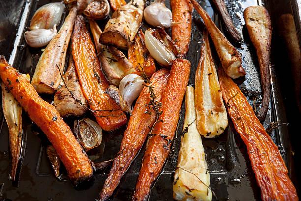 roasting carrots and parsnips with thyme - sjalot stockfoto's en -beelden