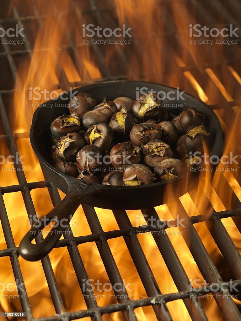 Roasting Chestnuts in a Cast Iron Pan stock photo