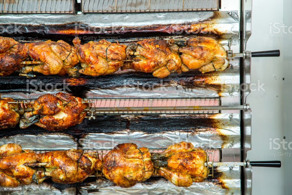 roasting chickens on a rotisserie at a market stock photo