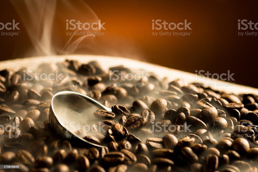 Roasting coffee beans with smoke on dark background stock photo