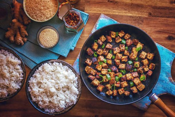 tofu mit soja-sauce und zwiebeln in einer pfanne rösten - mariniertes tofu stock-fotos und bilder