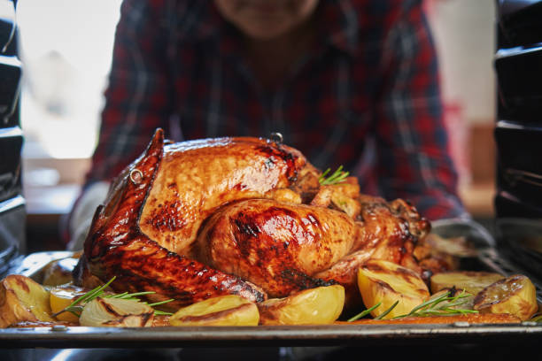 Roasting Turkey in the Oven for Holiday Dinner stock photo