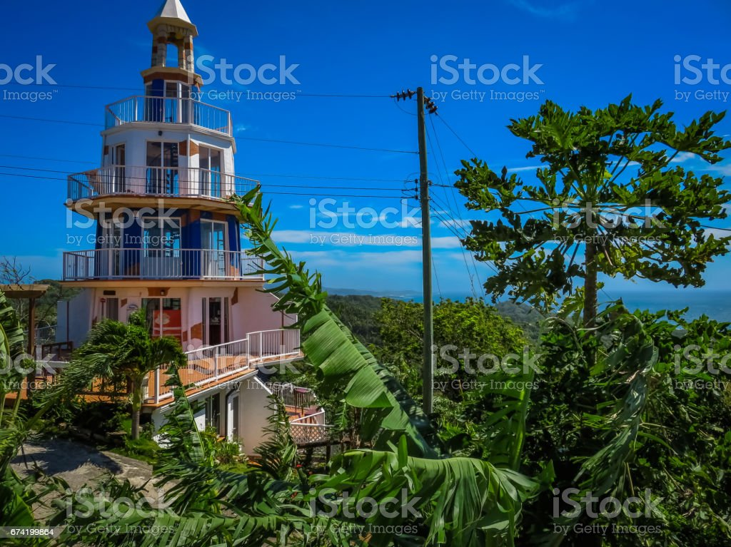 Roatan, Honduras Lighthouse building. Landscape of the island with a blue sky and green vegetation in the background. stock photo