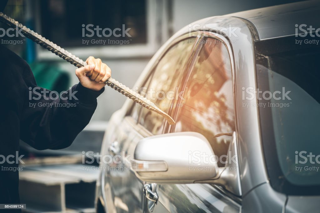 A robber dressed in black holding crowbar at a driver in a car. Car thief concept. stock photo