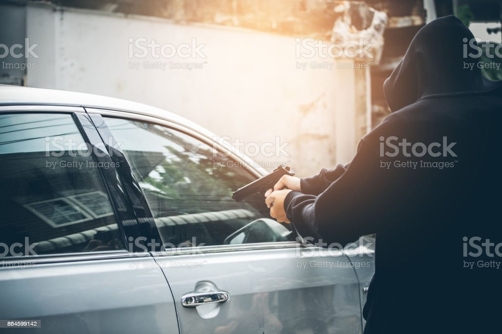 A robber dressed in black pointing a gun at a driver in a car. Car thief concept. stock photo