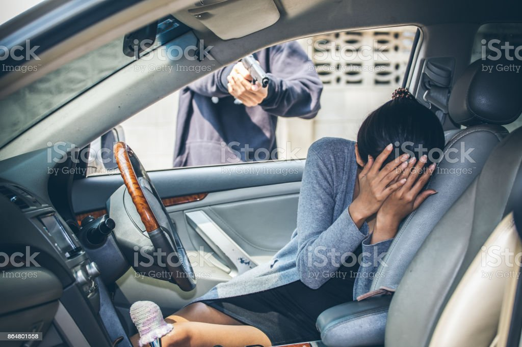 A robber dressed in black pointing a gun at a women driver in a car. stock photo