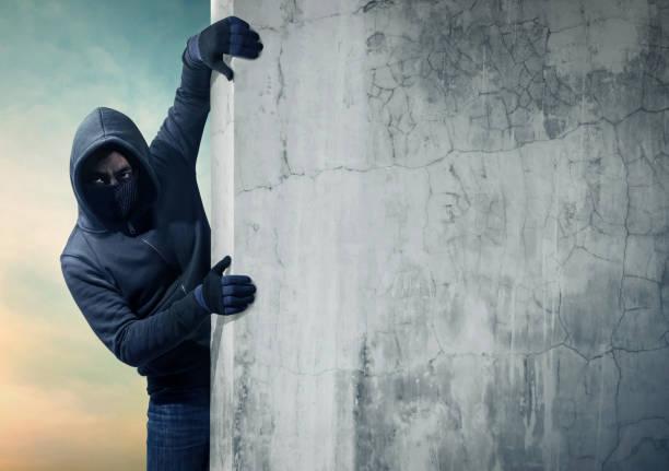 Räuber versteckt sich hinter einer leeren Wand mit Platz für text – Foto