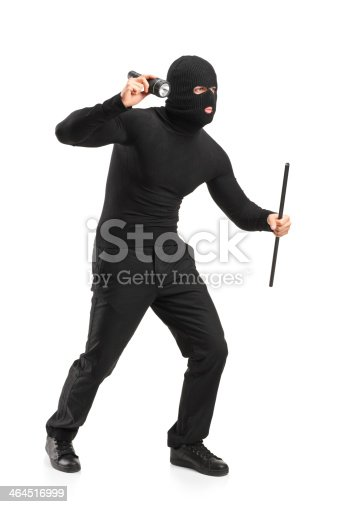 istock Robber holding a flashlight and piece of pipe 464516999