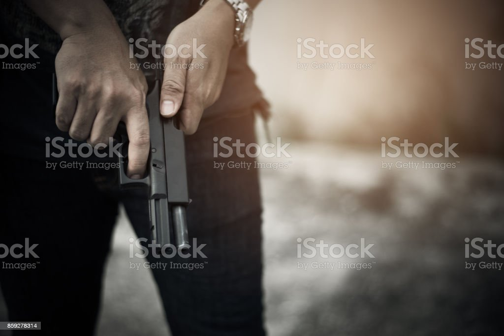 Robber holding gun for ready to murder steal moneys at abandoned building. Selective focus. criminality and social issues concept. Dark and low key tone tone pinterest and instragram like process. stock photo