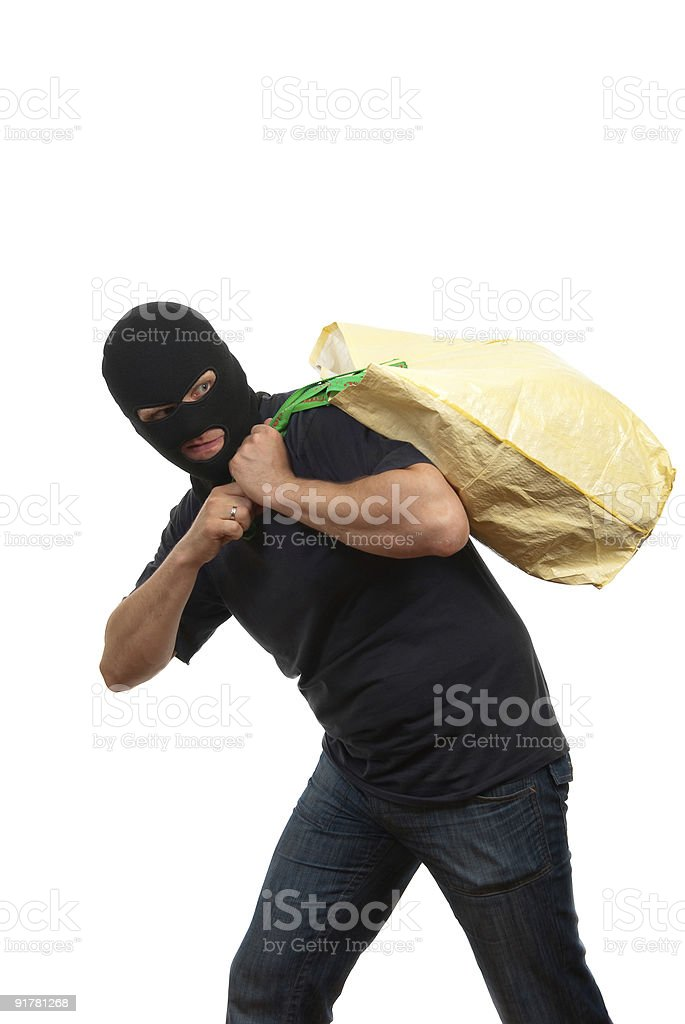 Robber in a mask carries big bag with money royalty-free stock photo