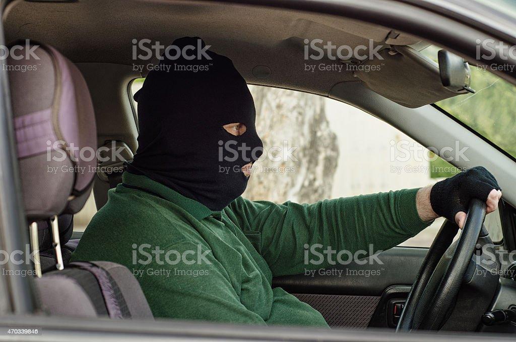 Robber in balaclava inside a car stock photo