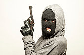 Armed robber with gun and ski mask.