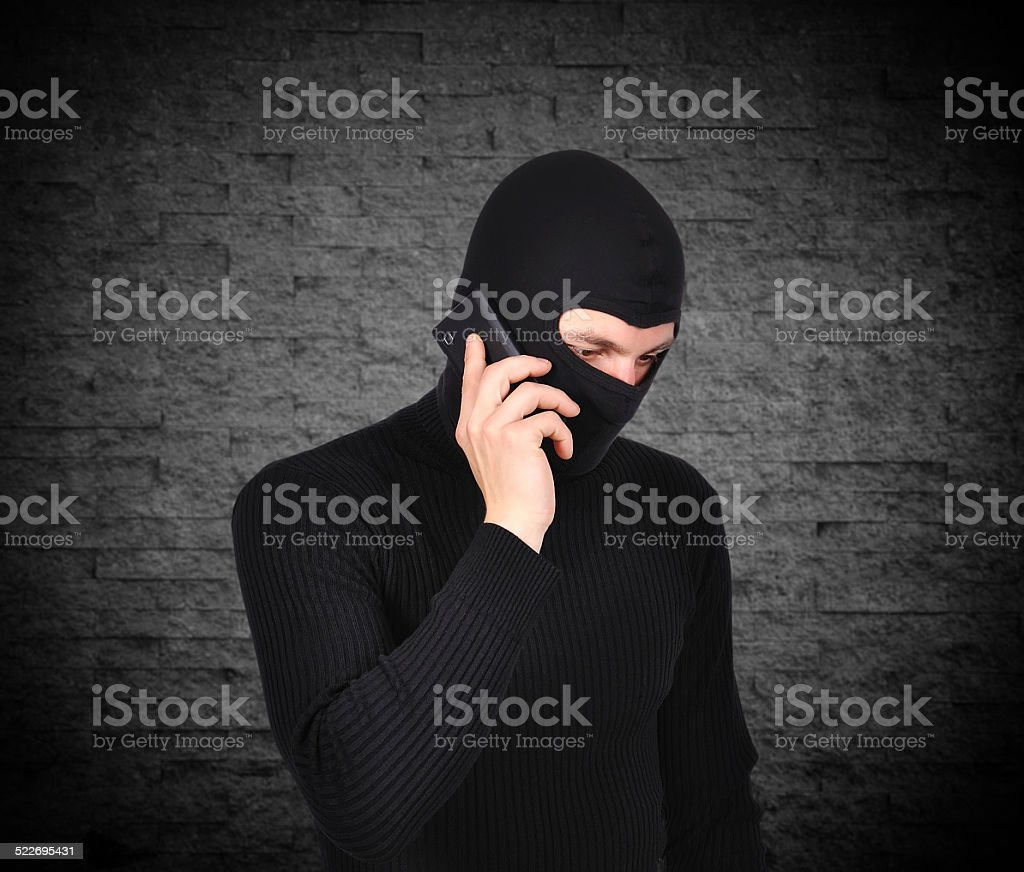 robber talking on phone stock photo