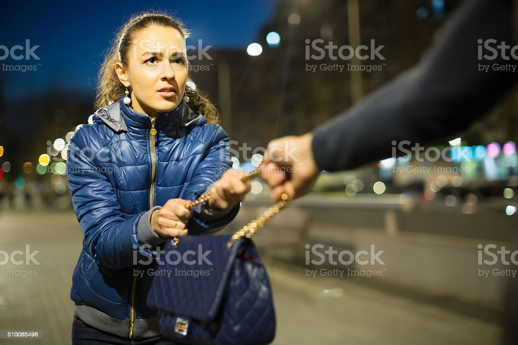 Robber trying to steal bag at night stock photo