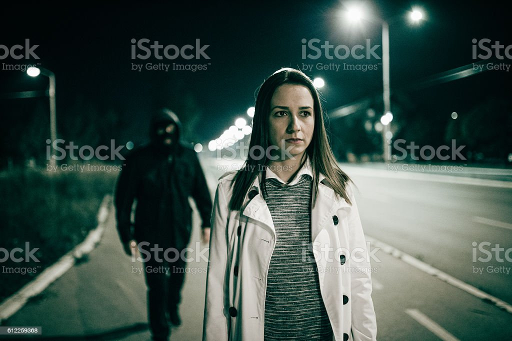 Robber walking behind a girl stock photo