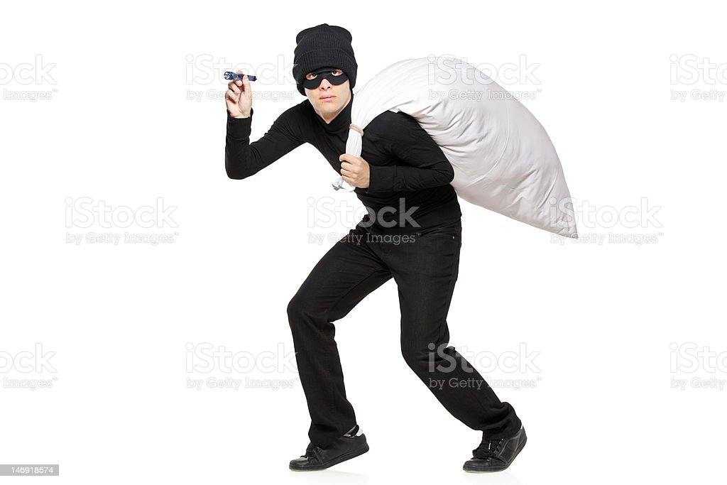 Robber with a bag and flashlight in hands stock photo