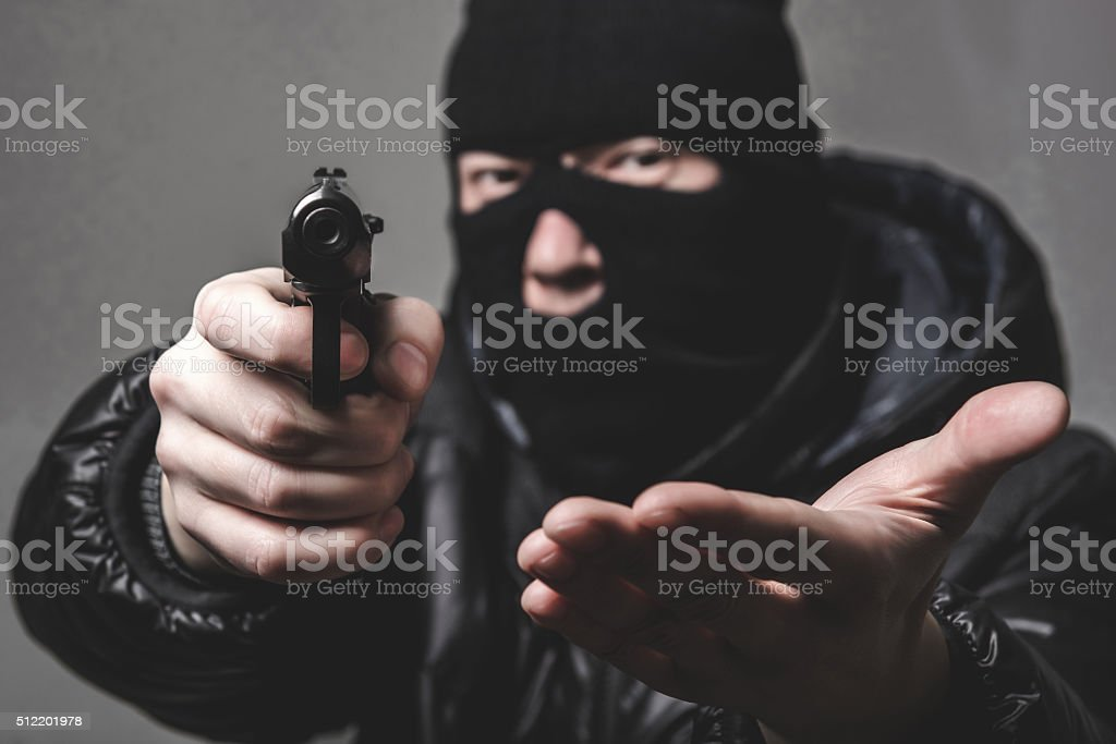 Robber with an aming gun stock photo