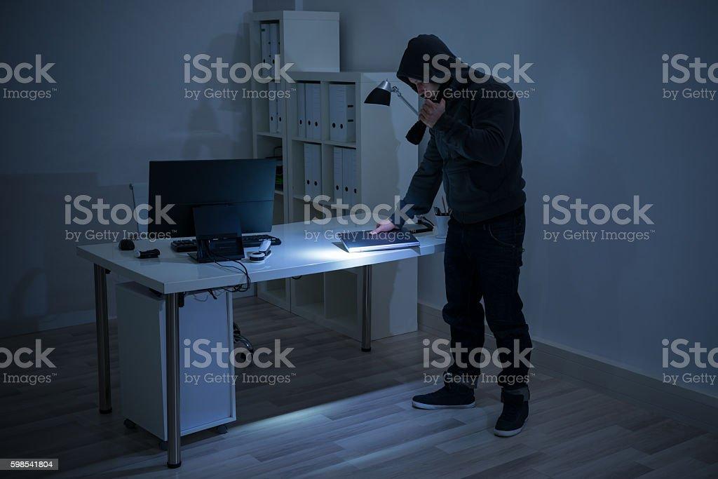Robber With Flashlight Holding Laptop At Desk photo libre de droits